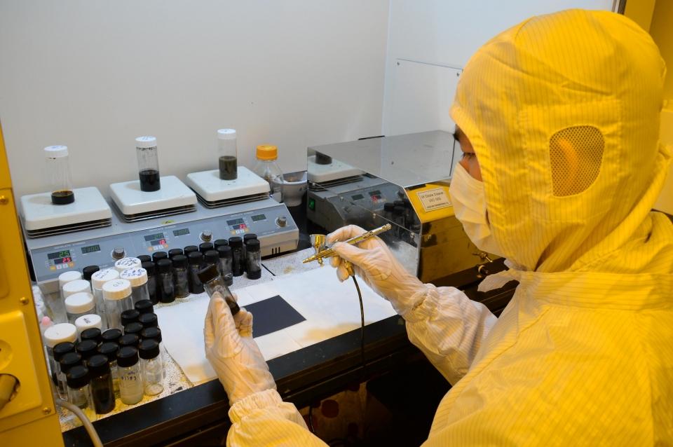 ETRI 탐반누엔 UST 학생이 전도성 나노 소재를 유연 플라스틱 기판 위에 스프레이 코팅하는 모습